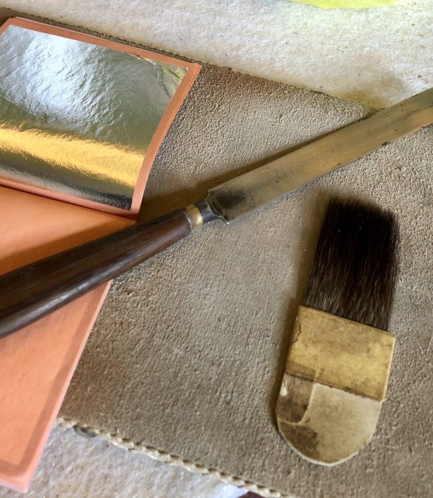 foto 5 Foglia argento con pennello di Vajo coltello e cuscino da doratore 891x1024 RESTAURI REALI, TORNA L'ORO SUI PORTELLONI DELLA REGGIA DI CASERTA